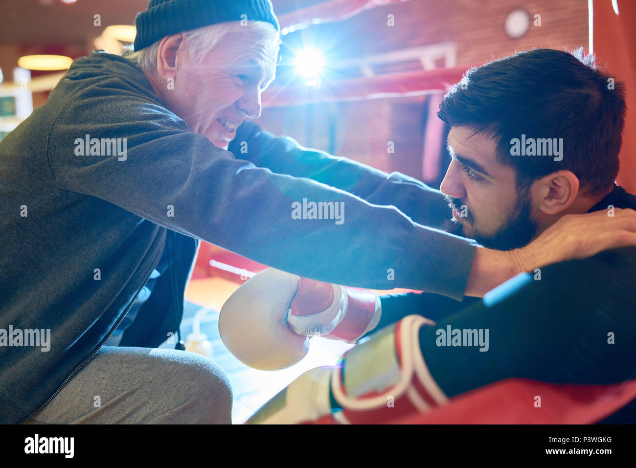 Professional trainer inspiring boxer - Stock Image