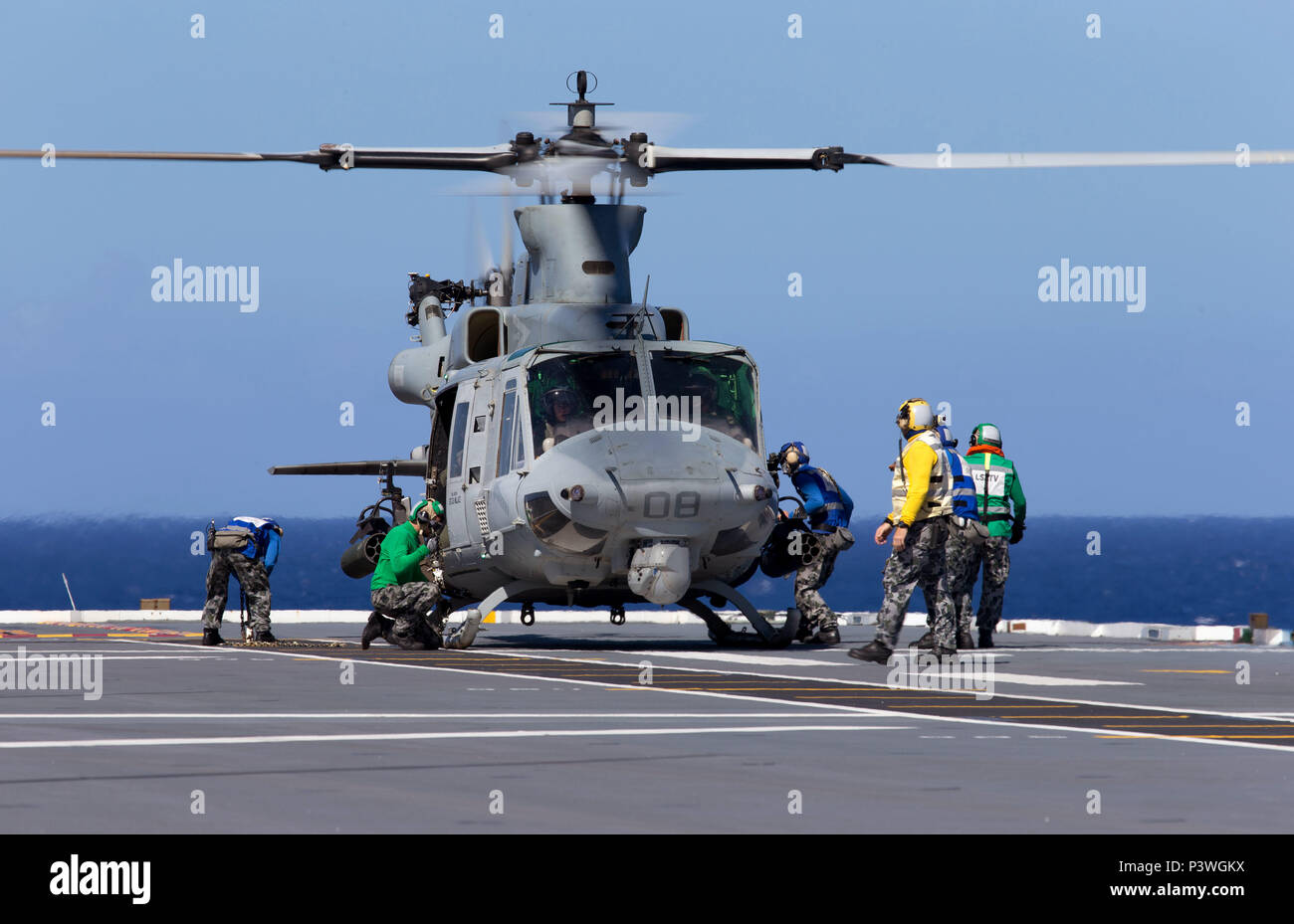 HMAS Canberra's flight deck crew secure a United States Marine Corps UH-1Y Venom medium utility helicopter on the flight deck of HMAS Canberra during Exercise Rim of the Pacific (RIMPAC) 2016. Rim of the Pacific (RIMPAC) is a U.S. Pacific Fleet-hosted biennial multinational maritime exercise designed to foster and sustain international cooperation on the security of the world's oceans. (Australian Defence Force photo by POIS Yuri Ramsey) - Stock Image