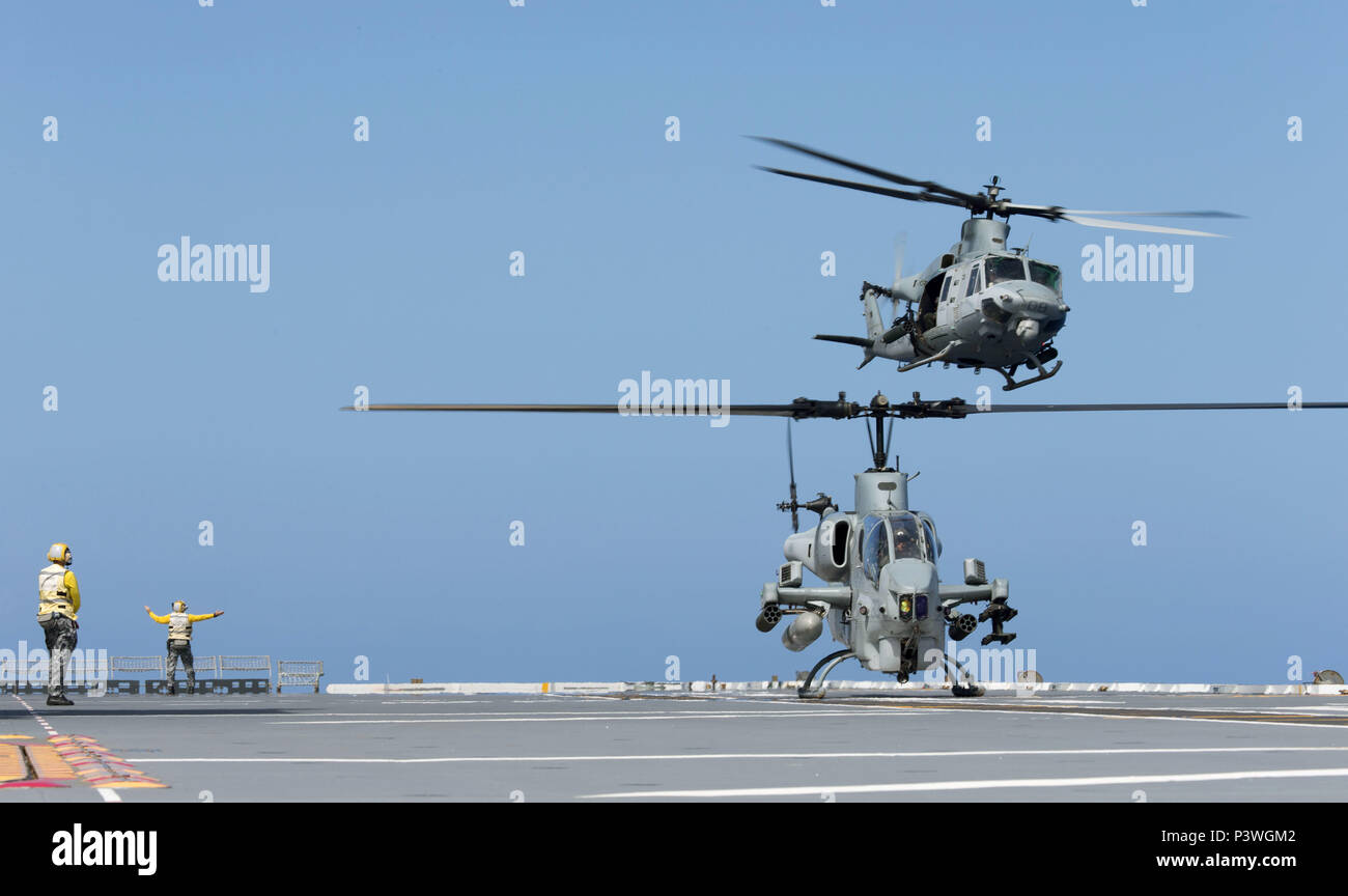 A United States Marine Corps (USMC) UH-1Y Venom medium utility helicopter takes off from HMAS Canberra as a USMC AH-1W SuperCobra helicopter waits in front during RIMPAC 2016. Rim of the Pacific (RIMPAC) is a U.S. Pacific Fleet-hosted biennial multinational maritime exercise designed to foster and sustain international cooperation on the security of the world's oceans. (Australian Defence Force photo by POIS Yuri Ramsey) - Stock Image