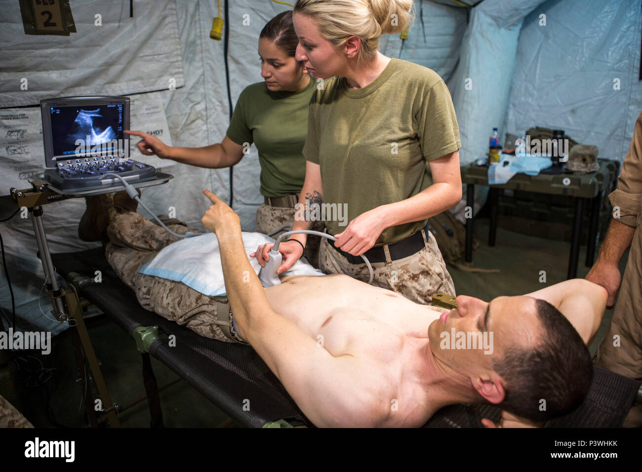 U.S. Navy Hospital Corpsman 2nd Class Ashley Tockweiler practices proper positioning procedures on U.S. Navy Lt. Cmdr. Robert Oldt, an emergency physician, both with Special Purpose Marine Air-Ground Task Force-Crisis Response-Africa using a Focused Assessment with Sonogram in Trauma exam, July 21, 2016. SPMAGTF-CR-AF medical personnel conducted FAST exams using a medical tent, or Shock Trauma Platoon, containing a surgical suite, called a Forward Resuscitative Surgical System, which makes it possible for forward deployed doctors to perform lifesaving surgical procedures in the event of a cris Stock Photo