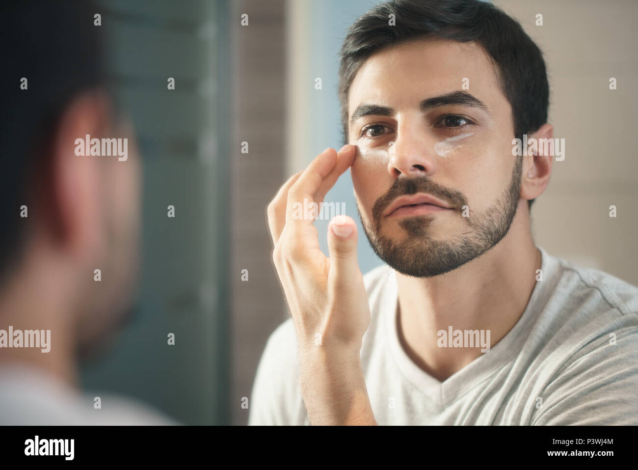 Young Man Applying Anti-aging Lotion fot Skin Care - Stock Image