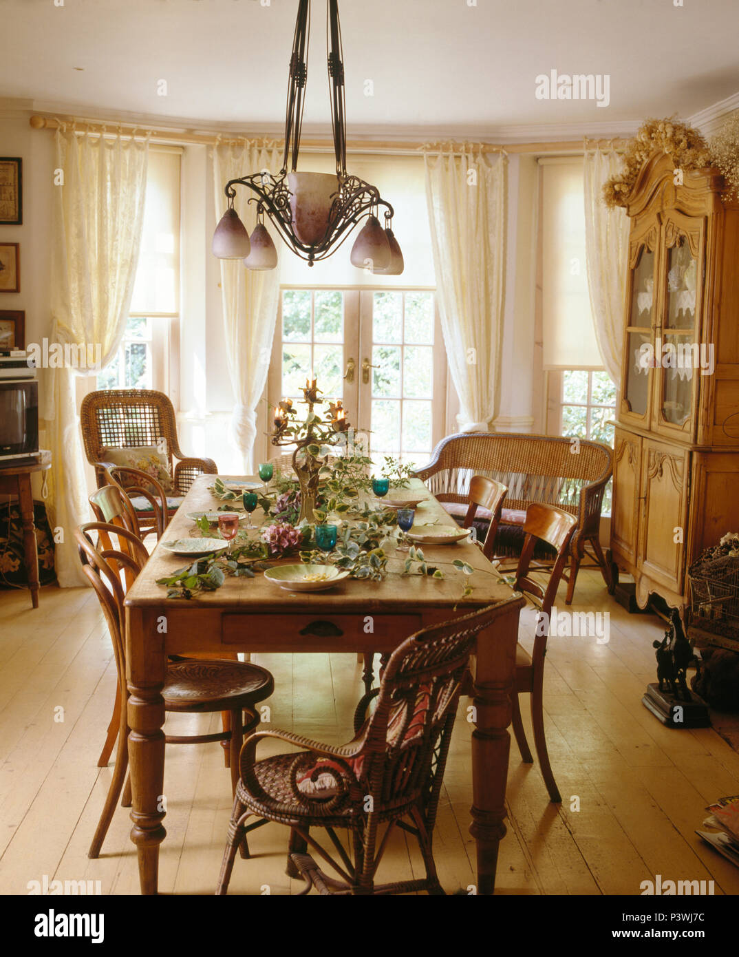 Art Nouveau Style Light Above Old Pine Table And Vintage Chairs In Country Dining Room With Wooden Floor White Drapes