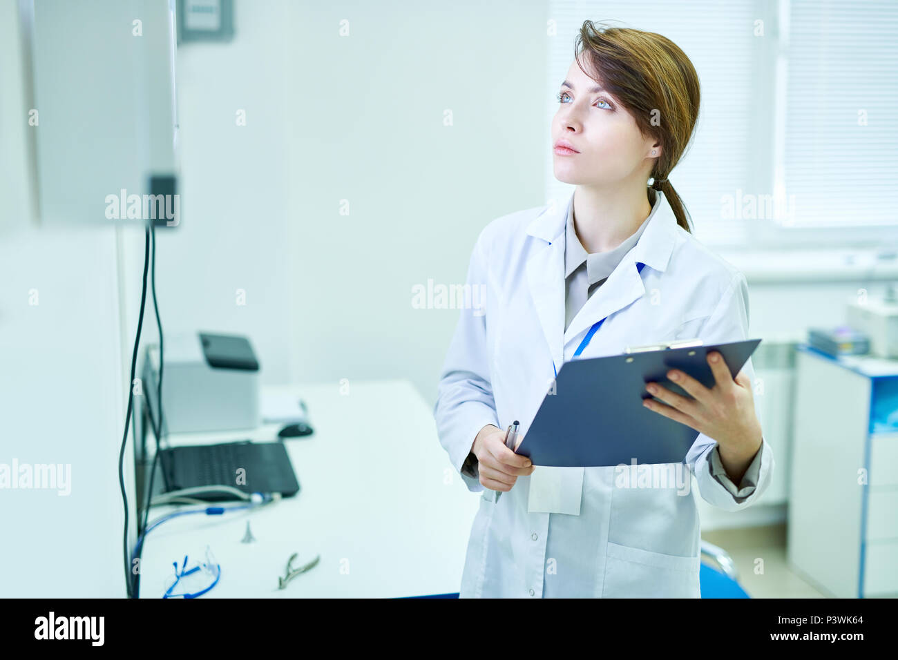 Doctor standing with clipboard and looking at something - Stock Image
