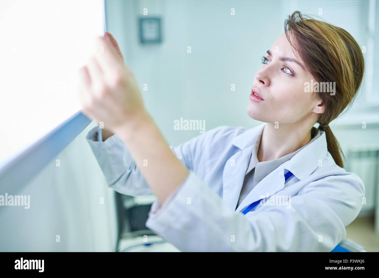 Doctor holding something and examining it - Stock Image