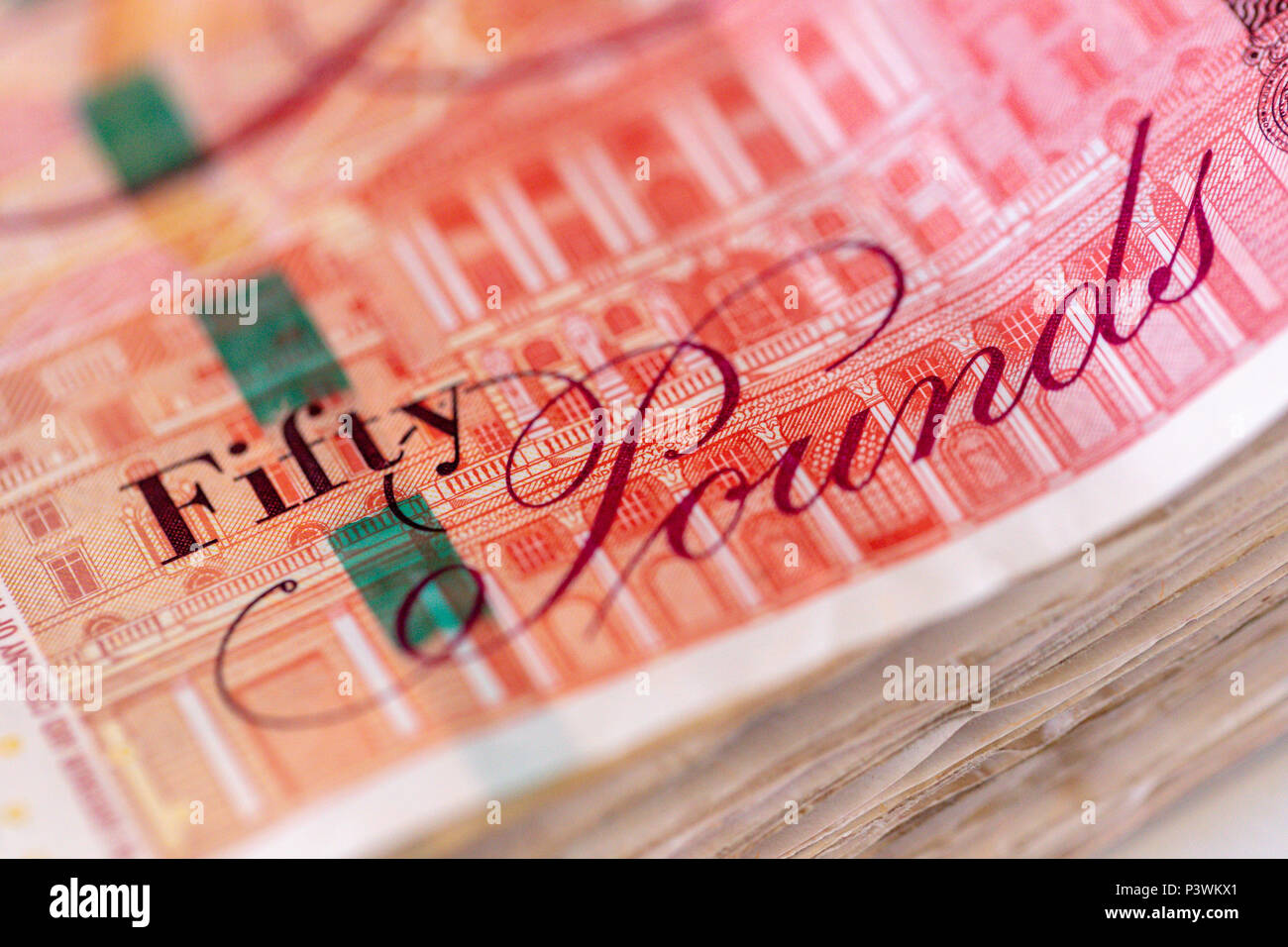 Background of a large pile of used fifty UK pound bank notes sterling Stock Photo