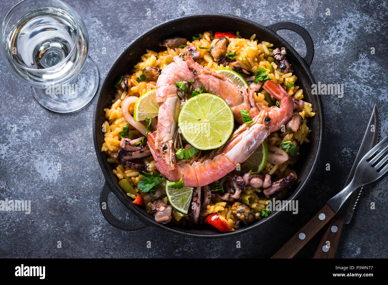 Seafood paella. Traditional spanish dish, european cuisine. Top view on dark stone table. Stock Photo