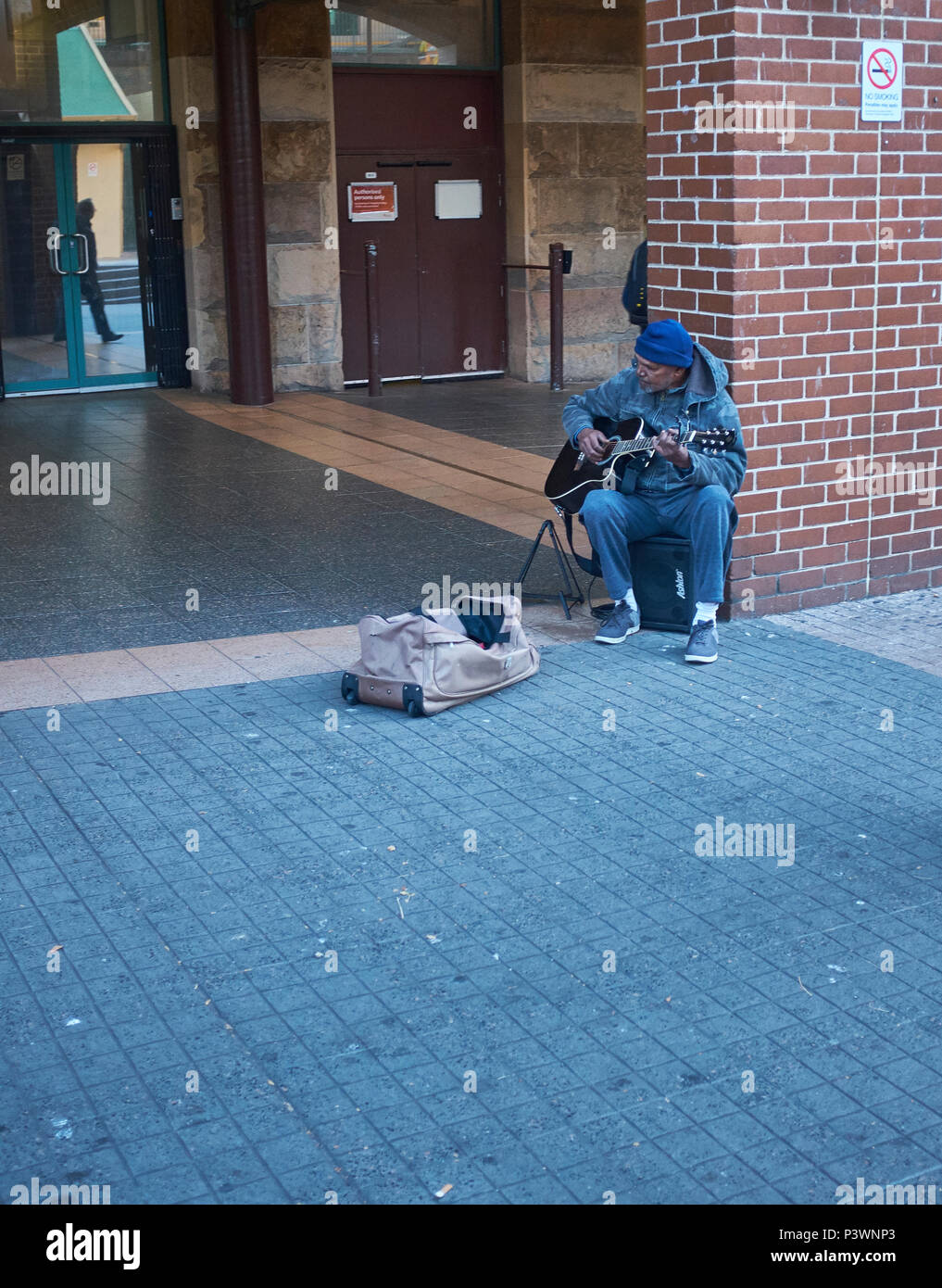 A busker sat on a loud speaker lent against a brick wall playing a guitar with a bag in front of him waiting for a donation, Sydney, Australia - Stock Image