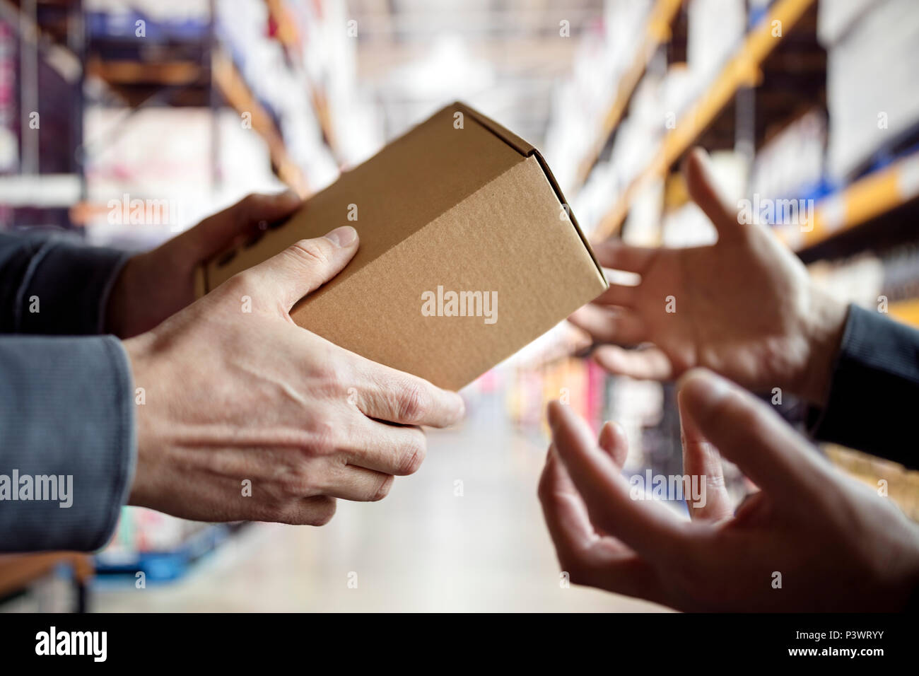 Worker giving a package in distribution warehouse - Stock Image
