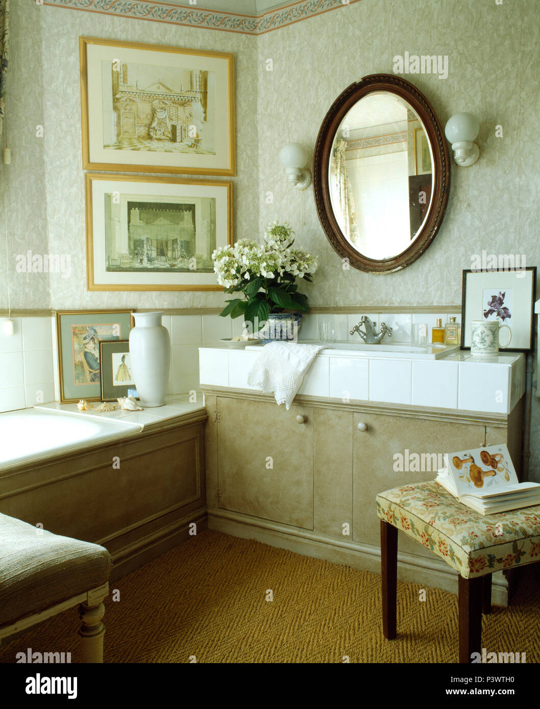 Oval Mirror On Wall Above Basin In Fitted Vanity Unit In Bathroom With Pale Grey Wallpaper Stock Photo Alamy