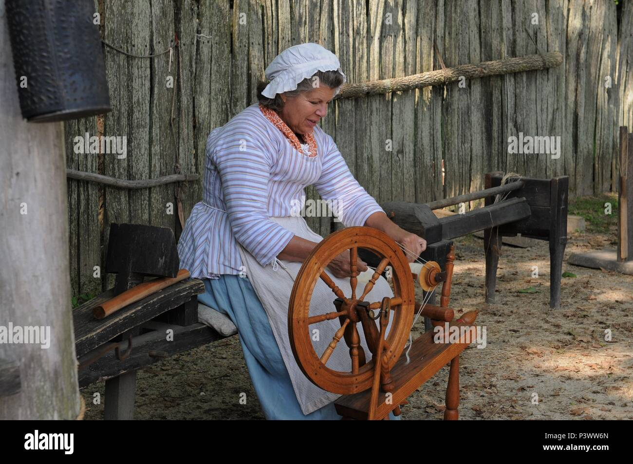 American pioneer spinning thread on a spinning wheel Stock Photo