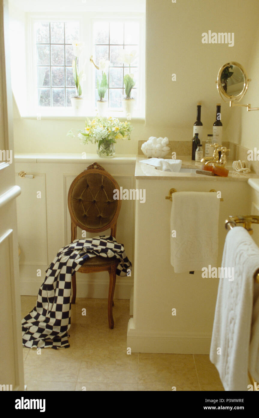 Black+white chequerboard towel on antique chair beside basin in vanity unit in cream cottage bathroom Stock Photo