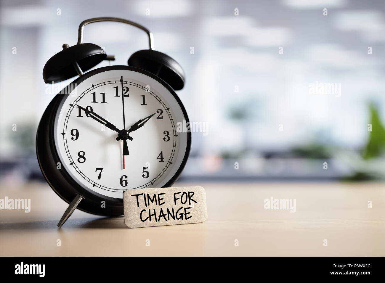 Time for change or action concept message with alarm clock on desk in office - Stock Image