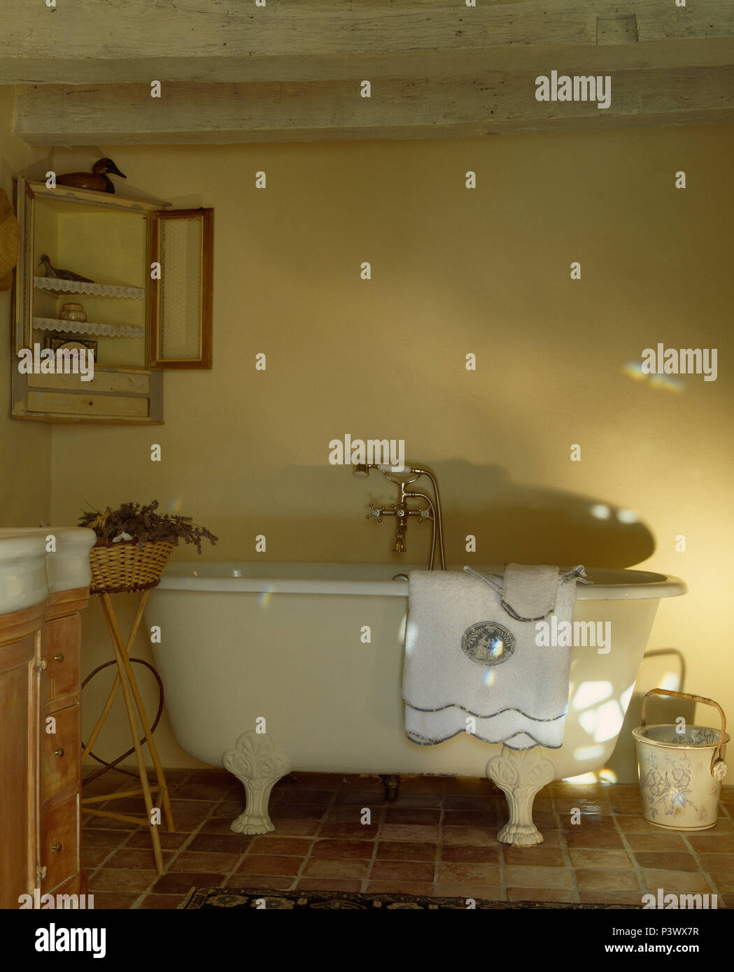 White towel on old claw-foot bath in pale yellow French country bathroom - Stock Image