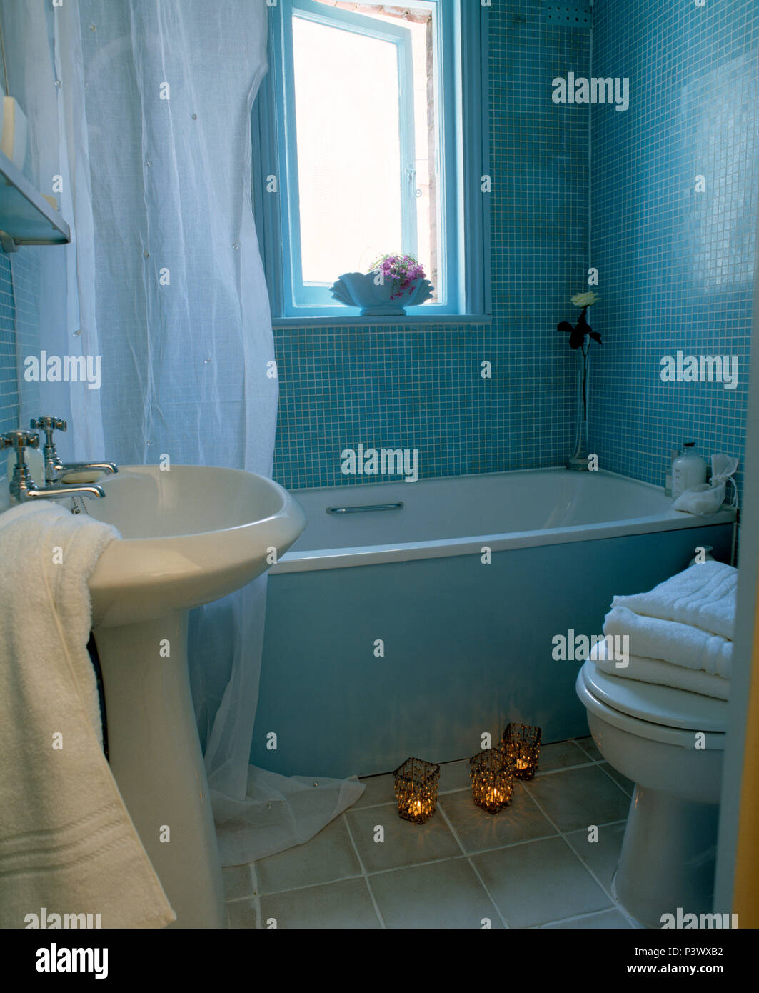 White shower curtain on bath in blue mosaic tiled bathroom with ...