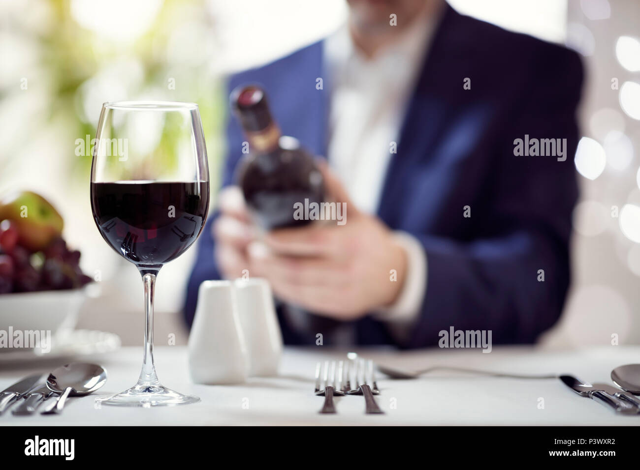 Businessman reading red wine bottle label in restaurant concept for business lunch or dinner meeting - Stock Image
