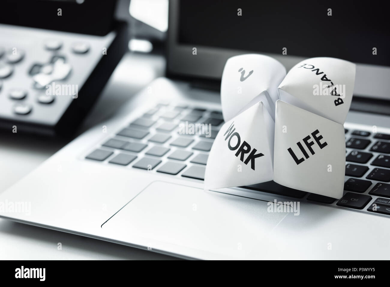 Origami fortune teller on laptop in office concept for work life balance choices - Stock Image