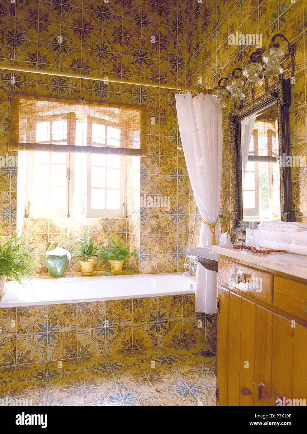 White Shower Curtain On Bath In Blue Yellow Tiled Bathroom With Open Windows Above The