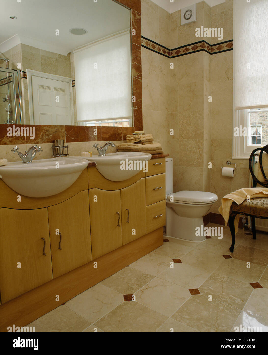 Large Mirror Above Pale Wood Vanity Unit With Double Basins In Marble Tiled Bathroom Stock Photo Alamy