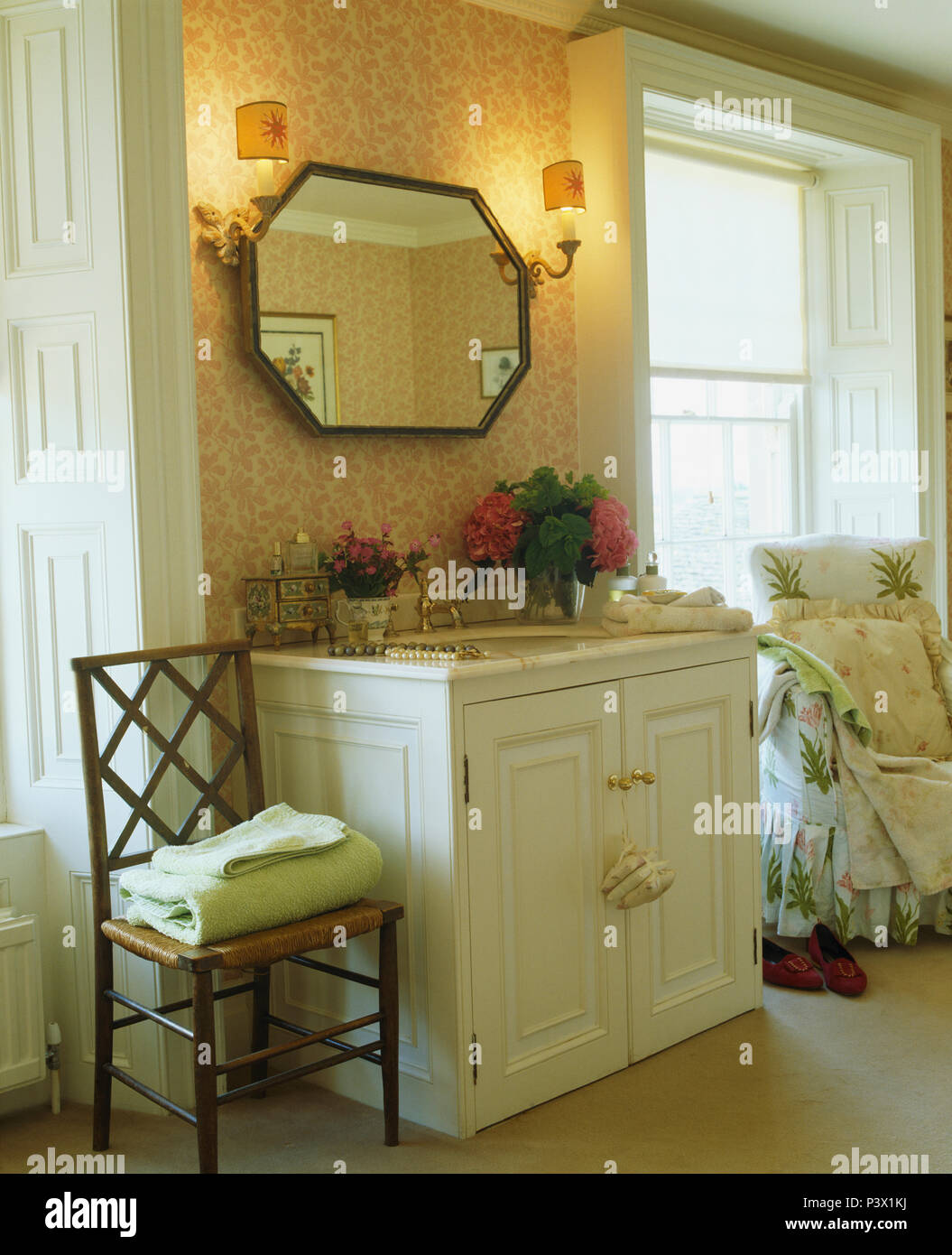 Bedroom with mirror between wall lights vanity unit with basinb - Stock Image