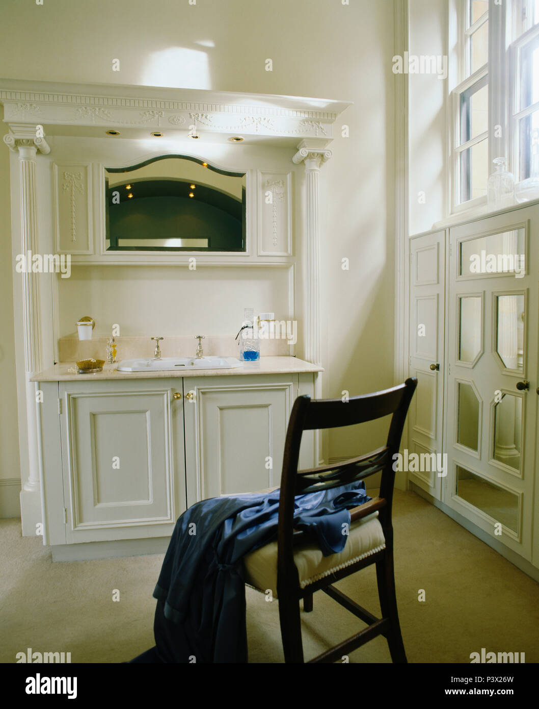 Mirror above fitted vanity unit in townhouse bathroom with blue robe on antique chair Stock Photo