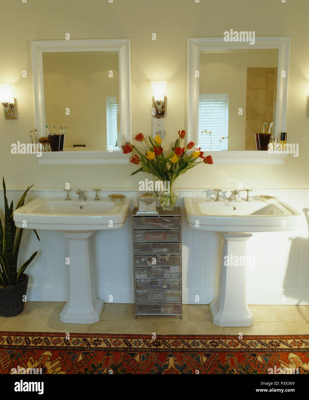 Mirrors above double pedestal basins on either side of narrow galvanised metal drawers in contemporary bathroom - Stock Image