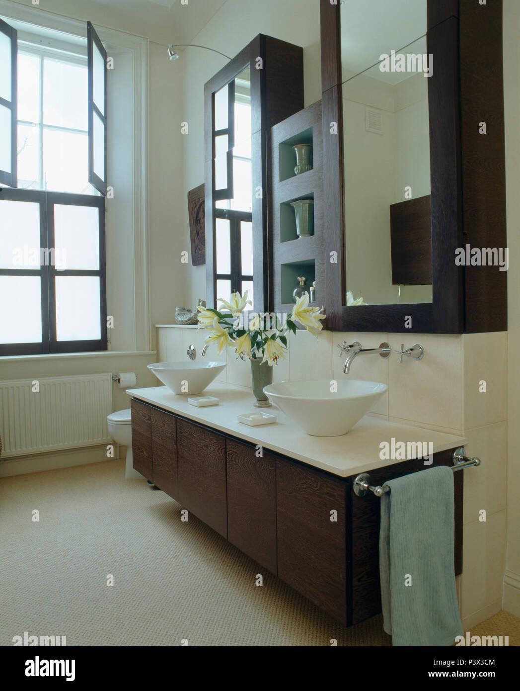White ceramic bowl-basins on vanity unit below mirrored cabinets in modern monochromatic bathroom - Stock Image