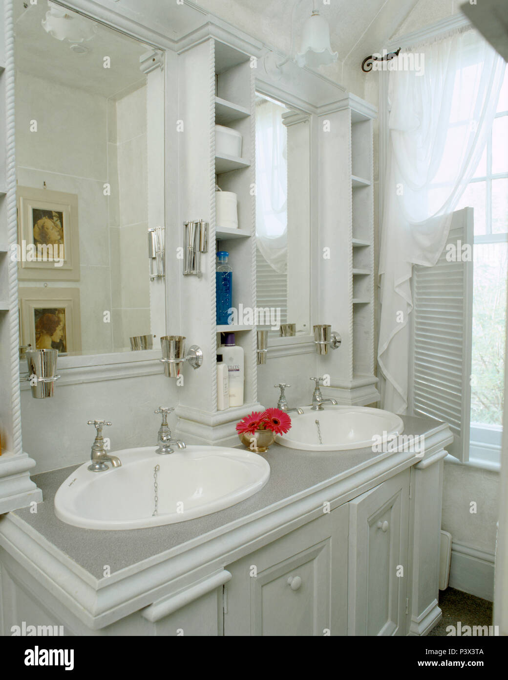 Storage Shelves And Mirrors Above Vanity Unit With Double White Oval Basins In Traditional Grey Bathroom Stock Photo Alamy