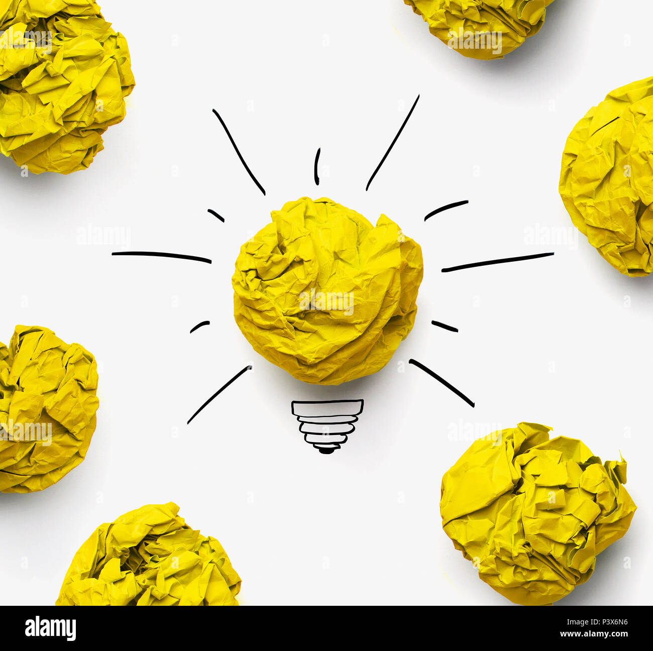 Great idea concept. Shining lightbulb between crumpled paper sheets with copy space - Stock Image