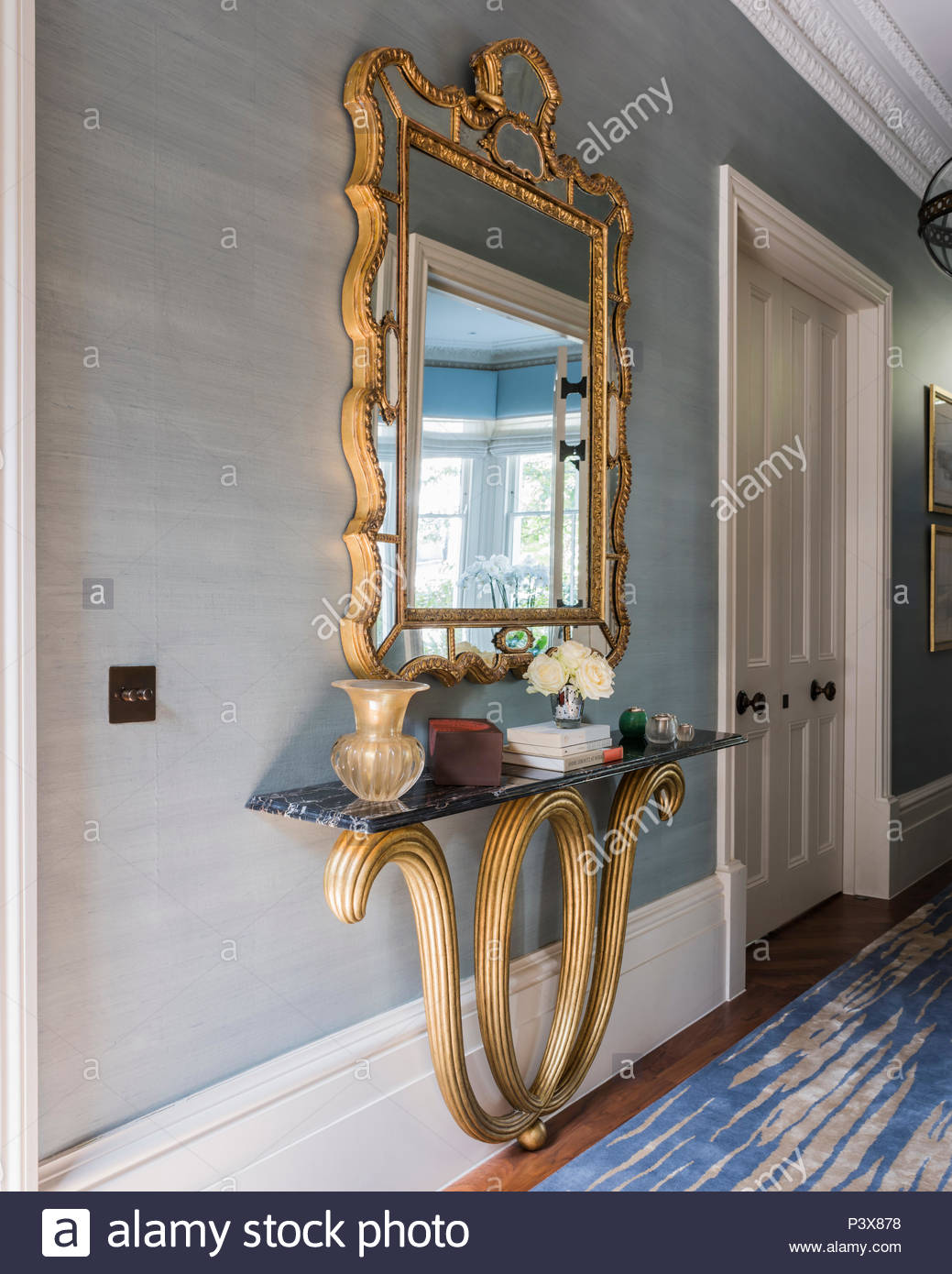 Large Gilt Framed Mirror Above Marble Shelf In Hallway Stock Photo