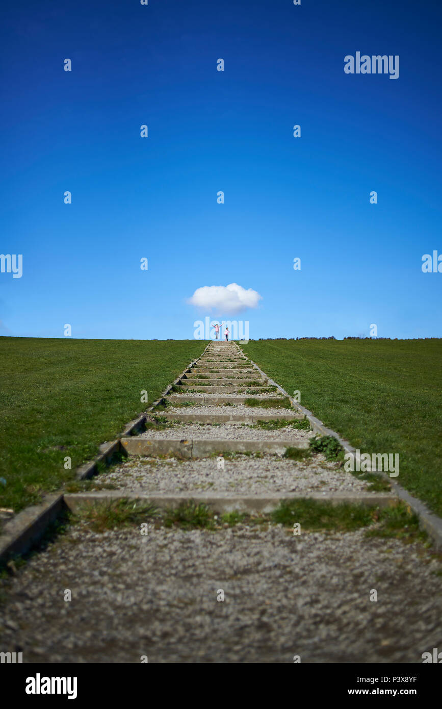 Landscape of a stairway to the horizon with two young children jumping in the distance with a cute white cloud hanging above them for protection - Stock Image