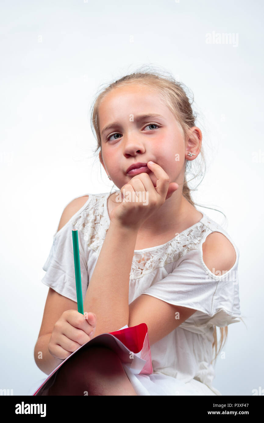 A cute 10-year-old caucasian schoolgirl thinking resting her face in her hand while holding a pencil and her note pad on her knee against a light back - Stock Image
