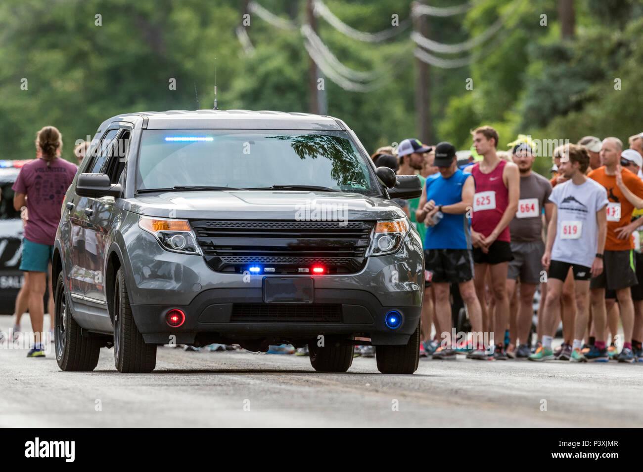 Police car leads runners in 5K & 10K foot races; annual Fibark festival; Salida; Colorado; USA - Stock Image