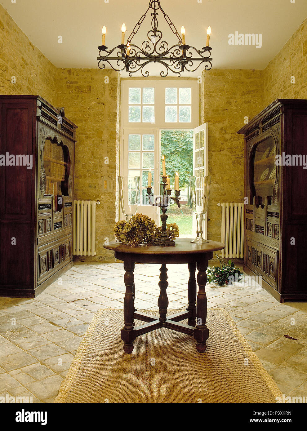 Sisal Rug On Stone Tiled Floor In French Country Dining Room With Oak Table And Dressers
