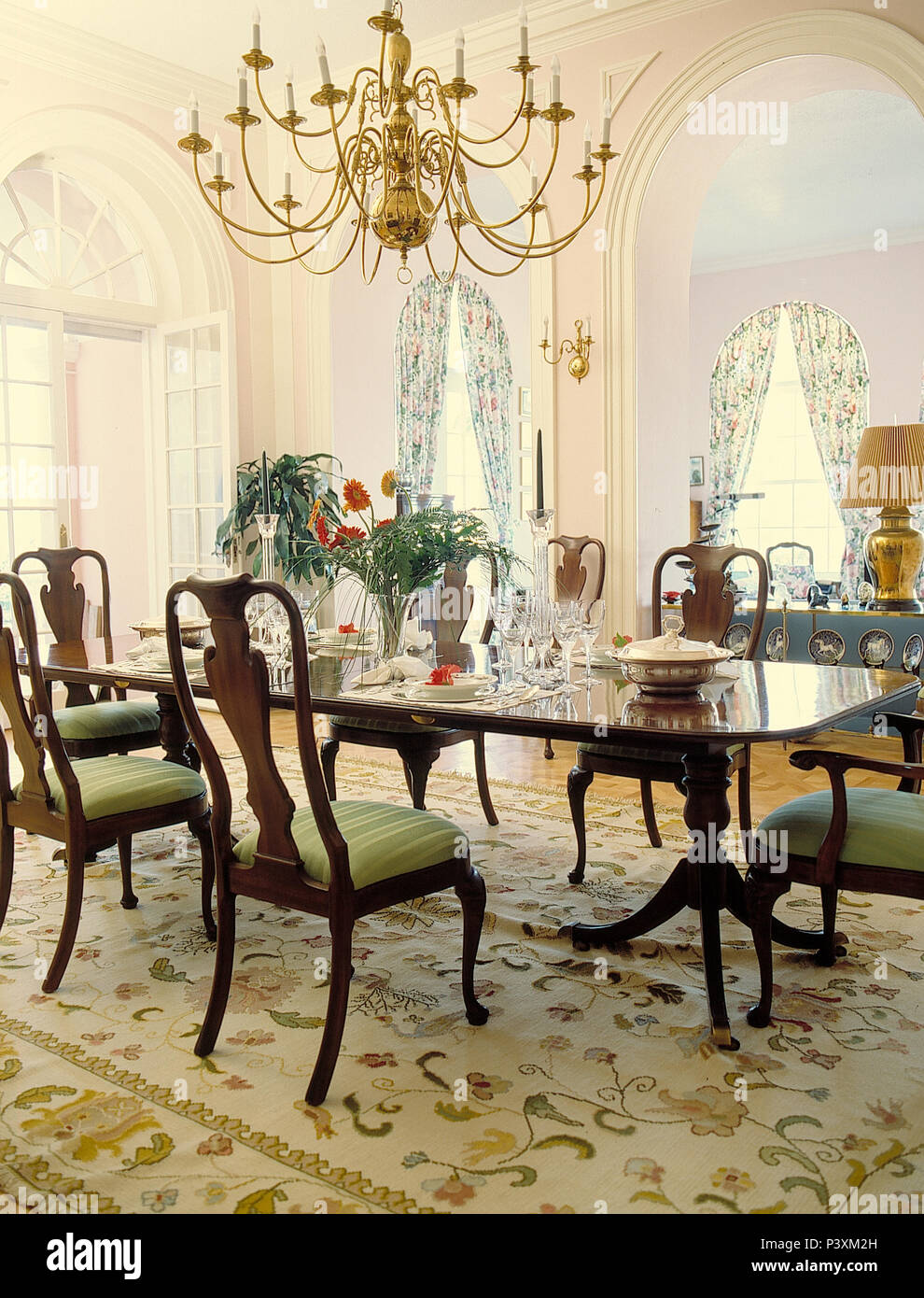 Chandelier Over Antique Mahogany Dining Table And Chairs In Opulent Dining Room With Pale Patterned Rug Stock Photo Alamy