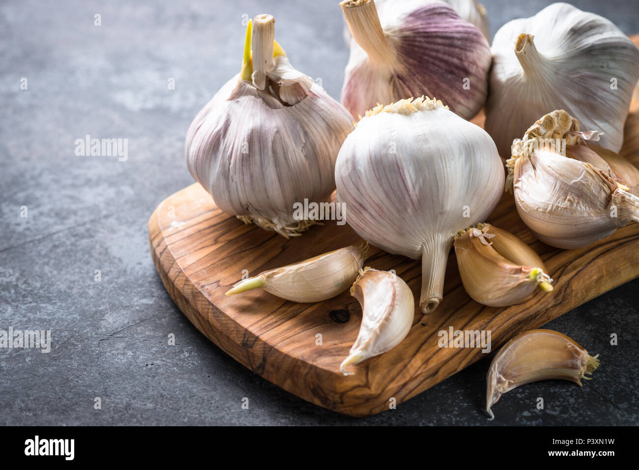 Garlic cloves on a dark stone background. - Stock Image