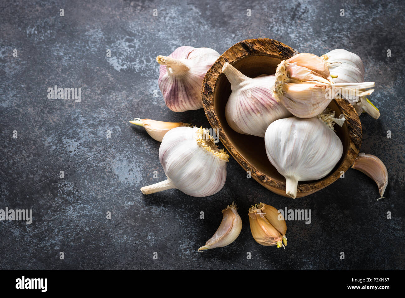 Garlic cloves on a dark stone background. Top view, Copy space. - Stock Image