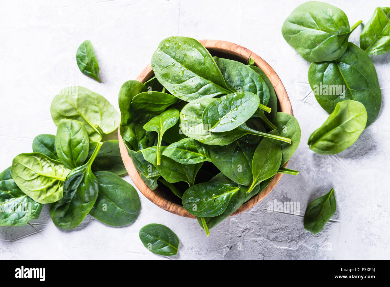 Baby spinach on gray stone table. Top view. - Stock Image