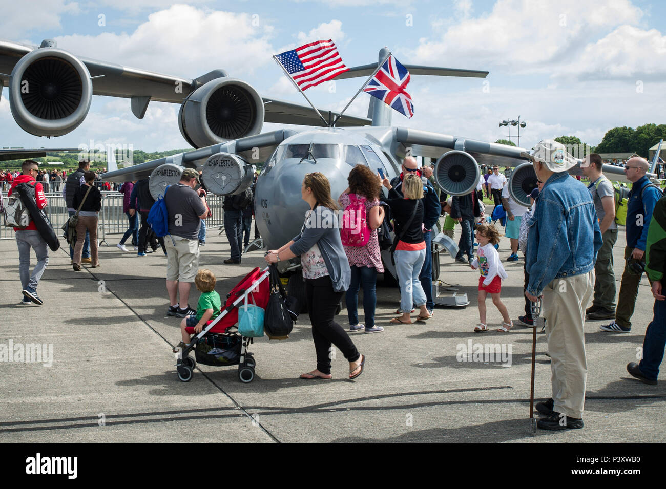 "Attendees of the Yeovilton, England crowd around the 315th Airift Wing's mini C-17 July 2. This was the mini C-17's first trip across the pond and was a huge hit at Yeovilton Air Day 2016. This is the 315th AWs second time visiting Royal Naval Air Station Yeovilton, England, and the mighty presence of the mini C-17 helped seal the deal for another ""Best Static Display"" award. The miniature C-17 has been used all across the United States to promote the Air Force Reserve and bolster recruiting efforts at air shows, parades and other community events. (U.S. Air Force photo by Master Sgt. Shane El - Stock Image"