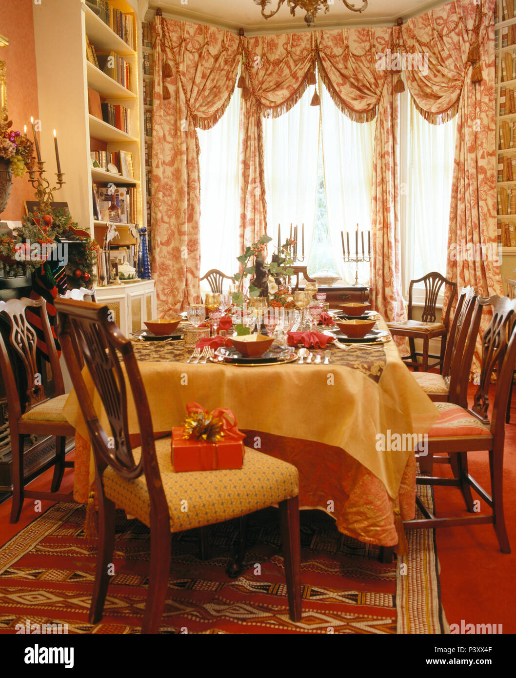 Swagged Patterned Curtains On Windows In Townhouse Dining Room Decorated For Christmas With Table Set Dinner