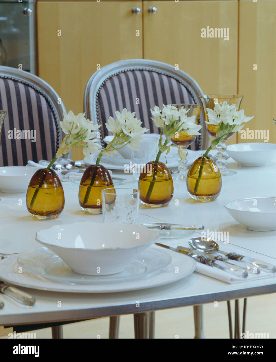 White flowers in row of amber glasses on white dining table with white crockery - Stock Image
