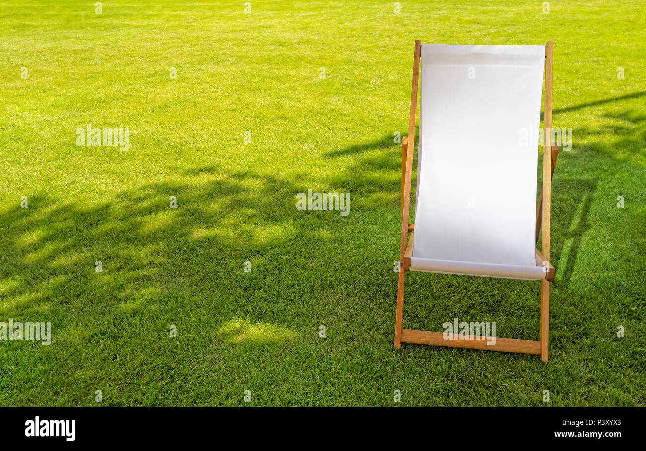 Single White Empty Deck Chair on Lawn - Stock Image