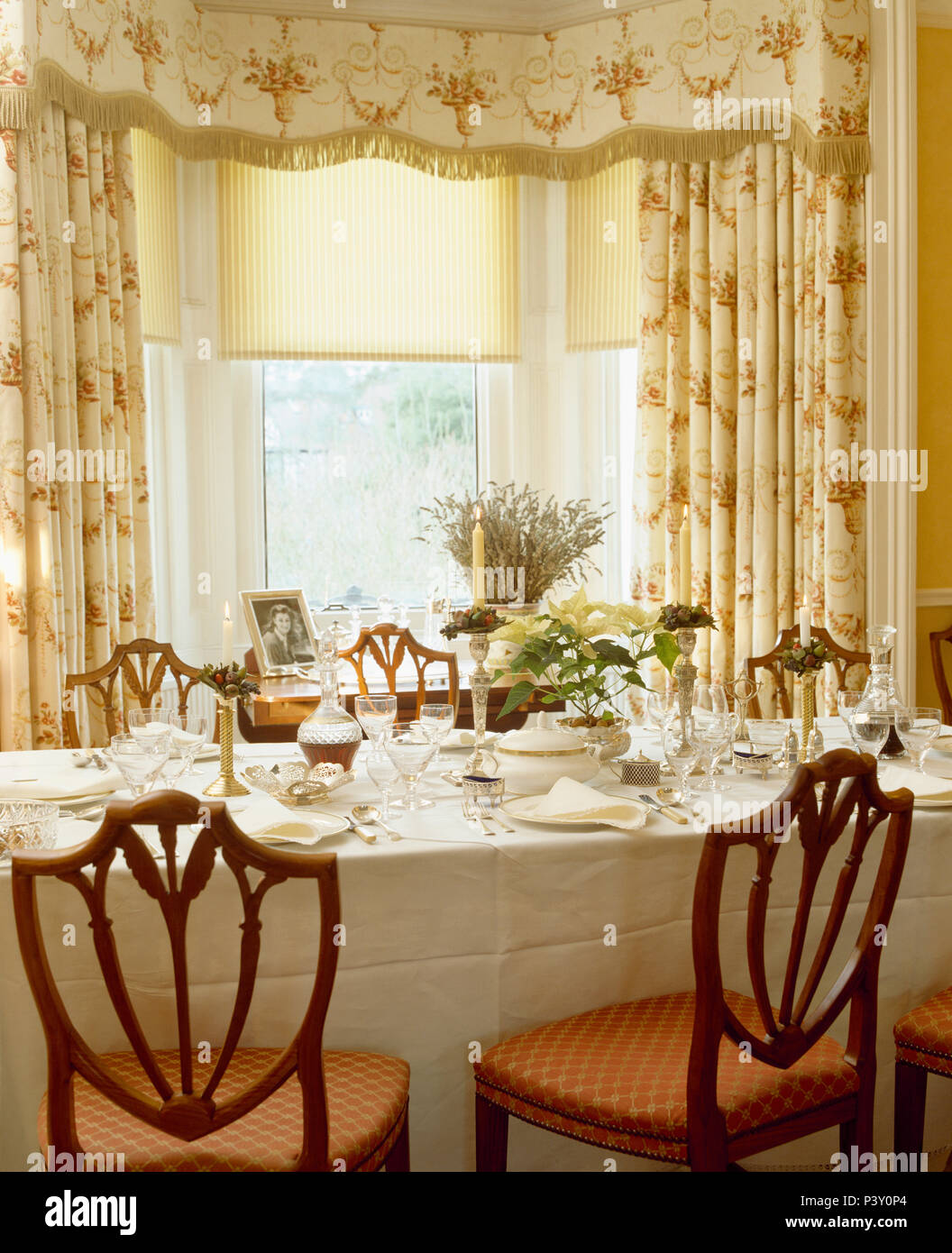 Cream Blind And Floral Curtains With Fringed Trim On Window In Dining Room With White Linen Cloth On Table Set For Lunch Stock Photo Alamy