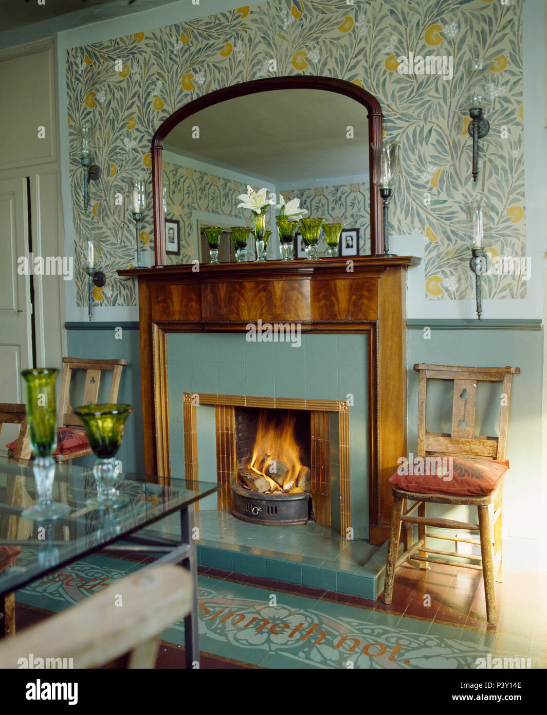 Stencilled Arts+Crafts pattern on wall above fireplace with lighted fire in country dining room - Stock Image