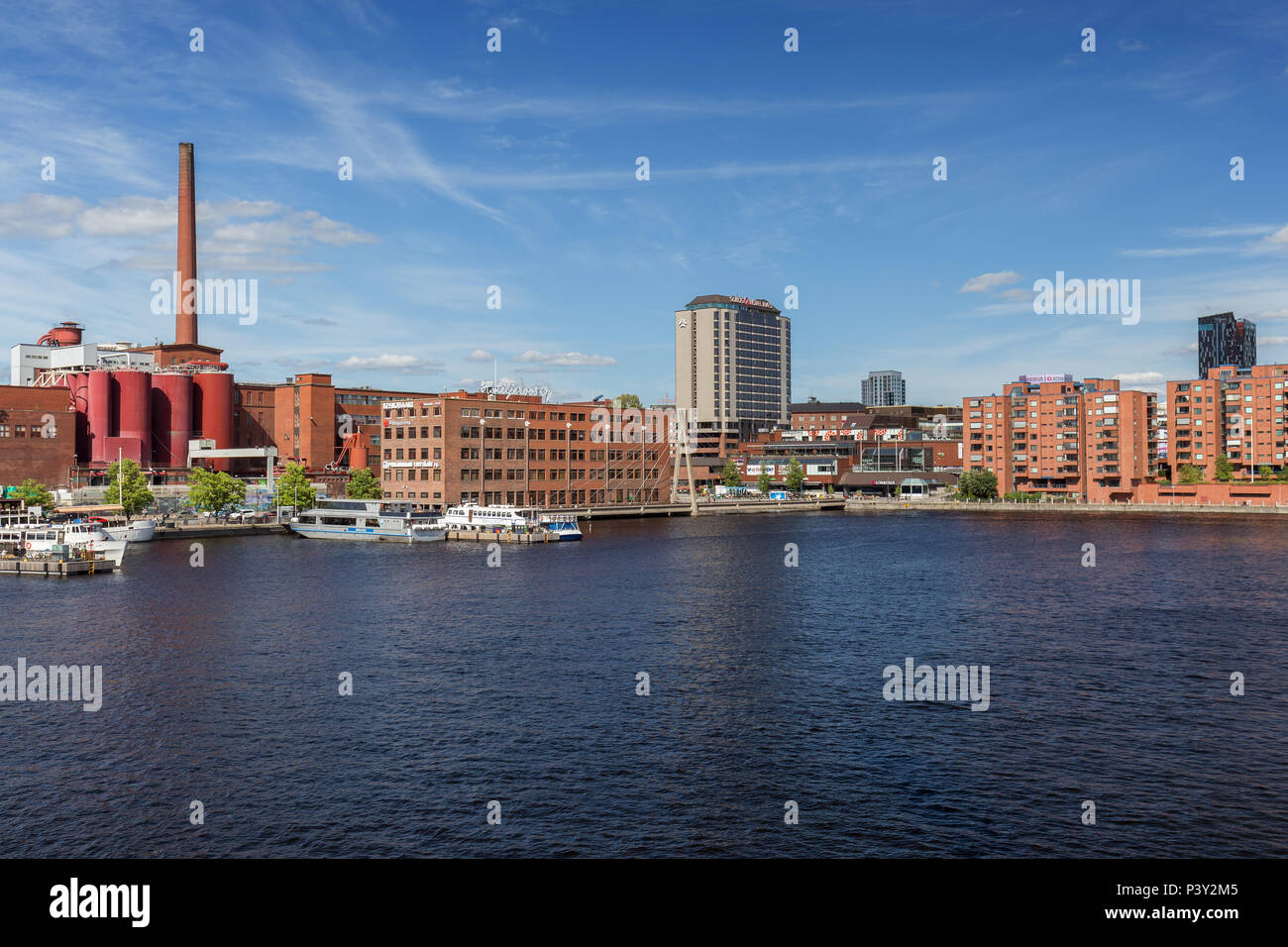 View of buildings and tourist boats at the Ratinan Suvanto (a bay or stream pool between Tammerkoski rapids and Lake Pyhäjärvi) in Tampere, Finland. - Stock Image
