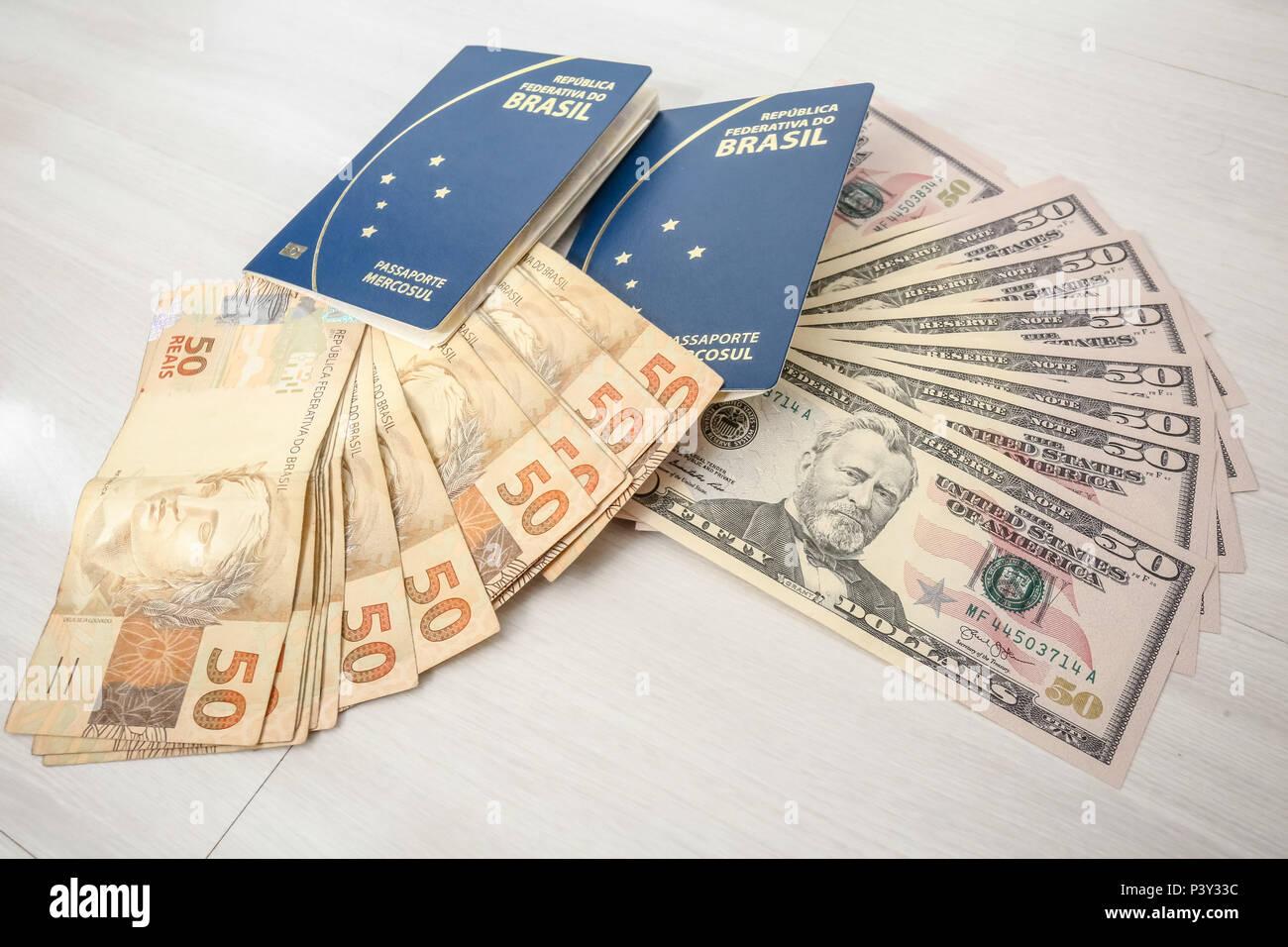 Dólar ao lado de passaporte. O dólar americano é a moeda emitida pelos Estados Unidos e tem sua emissão controlada pela Reserva Federal daquele país. O dólar é usado tanto em reservas internacionais como em livre circulação. Stock Photo