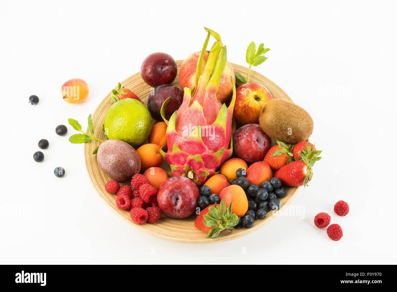 Obst, Früchte-Mix, Erdbeeren, Himbeeren, Blaubeeren, Äpfel, Birnen, Limette, Kiwi, Pflaumen, Aprikosen, Drachenfrucht und Minze - Stock Image