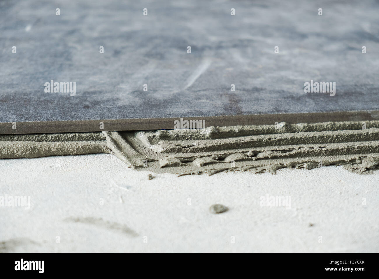 Dark Grey Ceramic Floor Tiles Laid On Applied Adhesive Stock Photo