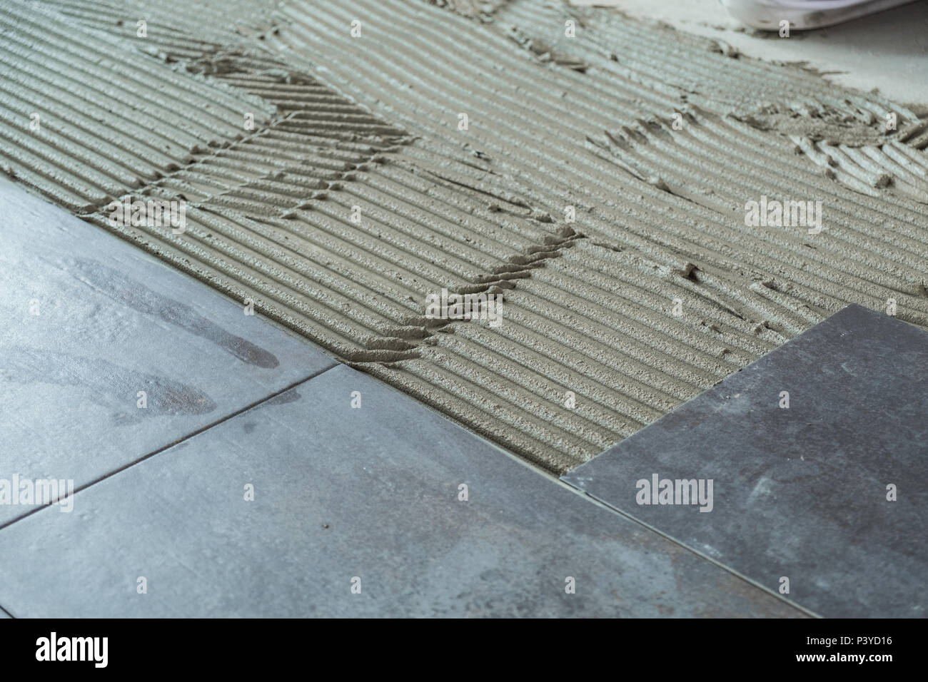 Dark grey ceramic floor tiles laid on applied adhesive Stock Photo ...