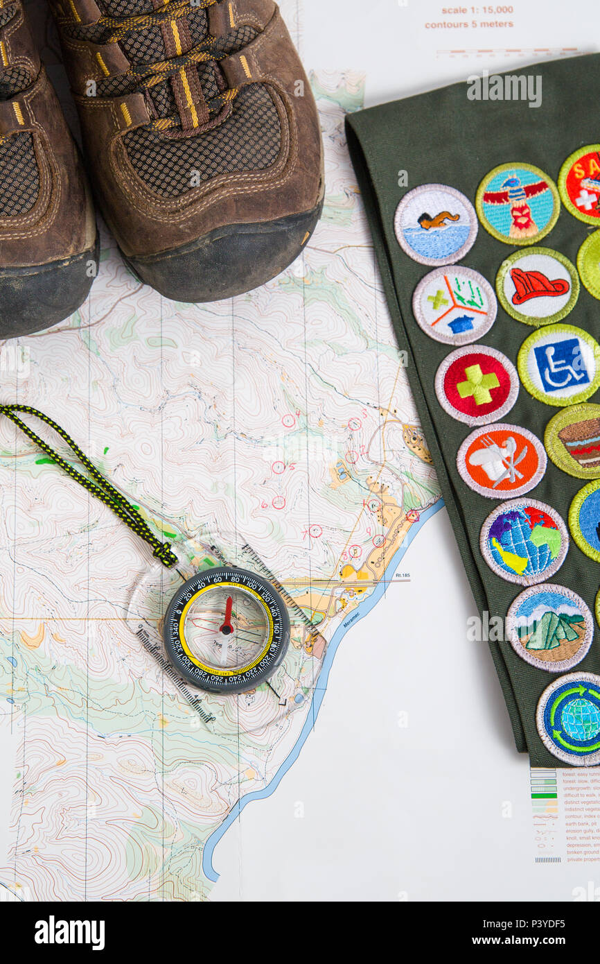 SAINT LOUIS, UNITED STATES - MAY 3, 2018:  Hiking boots, a compass, and a BSA merit badge sash rest on a map ready for a hike - Stock Image