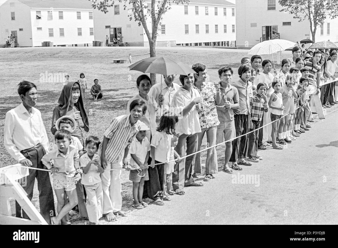 FORT SMITH, AR, USA - AUGUST 10, 1975 -- A line of newly-arrived Vietnamese refugees stand and wait for the passing of President Gerald Ford.  The president is to be touring the Fort Chaffee Vietnamese refugee center and welcoming the evacuated South Vietnamese to the United States.  Behind the people stands a row of the barracks buildings that housed the refugees.  Focus is on the center of the line of people. - Stock Image